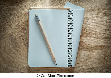 Spiral notebook pencil on wooden board office concept
