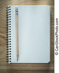Spiral notebook pencil on wooden board