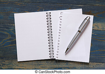 spiral notebook with pen on wooden background