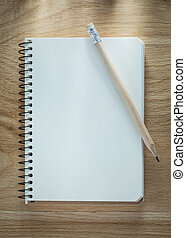 Spiral notepad pencil on wooden board