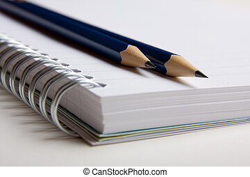 A pad with pencils on it ready to use