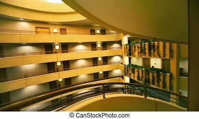 Spiral staircase in multiple floor hotel, downward motion