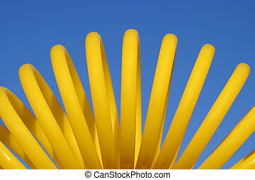 A coiled yellow air hose against the blue sky.