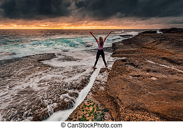 Spirited girl standing over rock crevice as waves wash in - ...