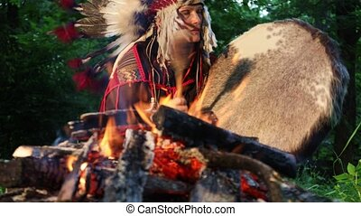Shaman woman in native American Indian clothes playing her shaman sacred drum at night in the forest. Ethnic traditions