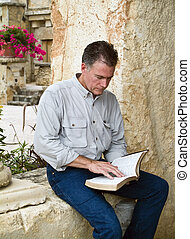 Spiritual Repose - A man sitting and reading what appears to...