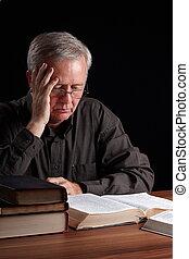 Spiritual searching - Senior pastor reading, meditating and...