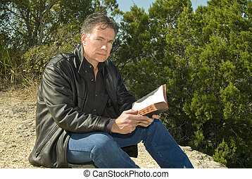 Spiritual Thoughts - A man with bible in his hand sitting...
