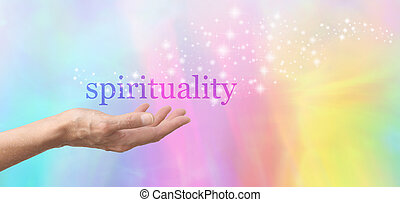 Female hand outstretched and facing upwards with the word 'spirituality' floating above on a rainbow colored background with sparkles flowing from the word