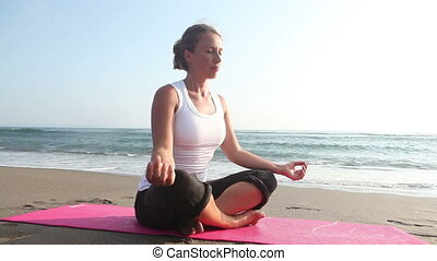 Spirituality woman sitting in pose lotus at coastline