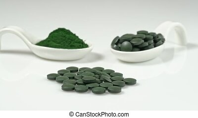 Spirulin in tablets and in powder on a table in ceramic spoons. Super vegetarian food