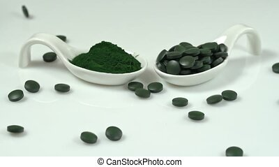Spirulin in tablets and in powder on a table in ceramic spoons, tablet in slow motion falling. Super food.