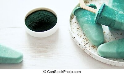 Superfood spirulina popsicles on white wooden tabletop. Ideas and recipes for healthy breakfast, summer vegetarian snack or vegan dessert. Popsicle with spirulina powder and coconut milk.