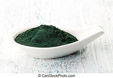 Spirulina powder in white porcelain spoon on white wooden...