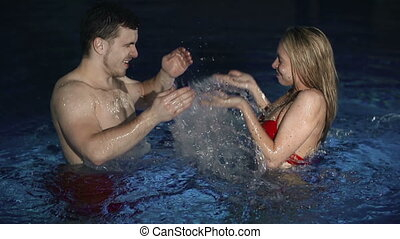 Splash Fight - Side view of couple enjoying their time in...