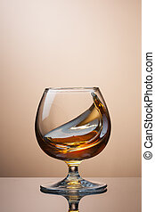 Splash of cognac in glass on brown background