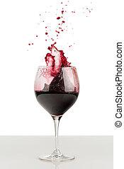 Splash of red wine in a wineglass. - Splash of red wine in...