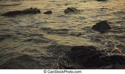 Splash of small waves on the rocks at sunset slow motion