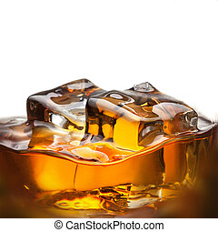 Splash of whiskey with ice in glass isolated on white