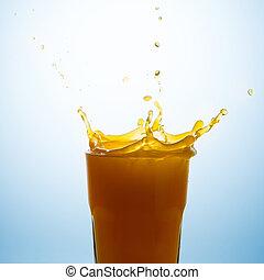 Splash on a glass of orange juice against a blue background