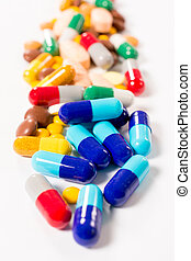 Splashed pills on white background - Selective focus in the...