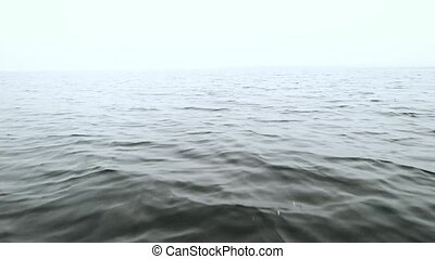 Splashes of water on the side of a fast moving boat on sea on a cloudy day