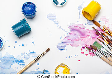 splashes of watercolor paint and painting supplies