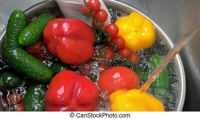 Splashing tap water on vegetables. Hands washing vegetables...