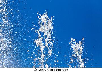 Splashing water against the blue sky