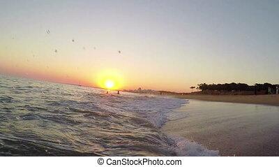 Splashing waves on a Portuguese beach, during sunset.