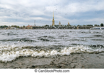 Splashing waves on the river Neva and view of Peter and Paul fortress in Saint-Petersburg.