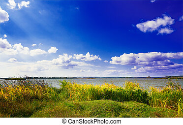 Wonderful autumn lake and blue sky with clouds.