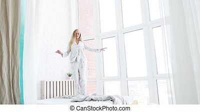 Splendid european female appearance, dance on the bed in good mood, new day happy and vibrant life. Woman wearing long robe.