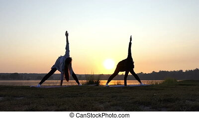 Splendid Sunset And Women Doing Yoga Exercise on a Lake Bank in Slo-Mo