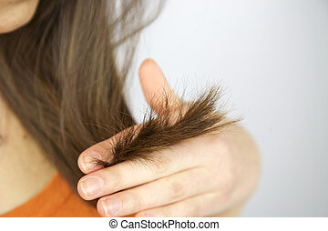 Split ends hair of brunette female model holding hand