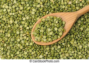 Split green peas background - Wooden spoon full of split...