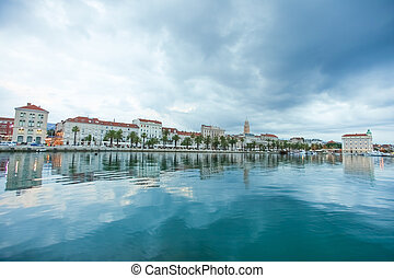 Split harbour in early morning with dark clouds and old town