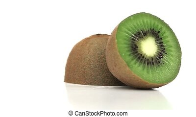 Split kiwi fruit rotating on a white background