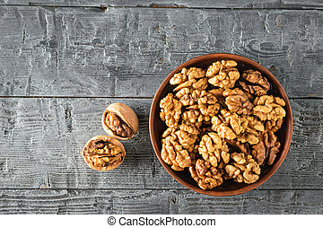 Split walnuts in a clay Cup on a wooden rustic black table. The view from the top. Flat lay.