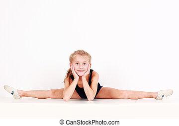 Cute little girl making splits on white background