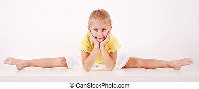 Splits - Cute little girl making splits on white background
