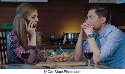 Spoiled date, young woman is calling on her mobile phone. Boyfriend is bored. Work call ruined romantic evening. Romantic dinner with wine and ice cream at home at night.