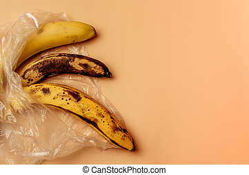 spoiled three bananas lie in a plastic bag on the table. Fruit concept in plastic. Life without waste and without plastic. Save the environment.
