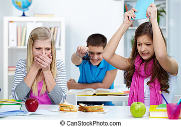 Spoiling appetite - Shocked girl looking at spider on one of...