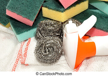Group of colourful sponge and metal cleaning scourers with green scrubbing surfaces.