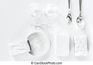 Sponge and tableware on white background top view copyspace