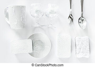Sponge and tableware on white background top view