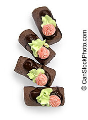 Several chocolate sponge cake with chocolate icing, pink flower and green leaf of the cream on a white background