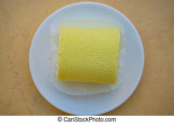 Sponge cake cream roll on white dish show bakery background