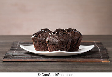 spongecake or muffin with chocolate sauce on wooden...